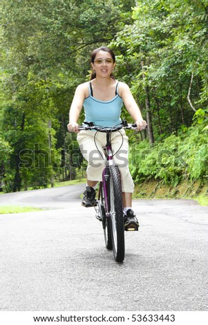 An Asian woman cycling on a road - stock photo