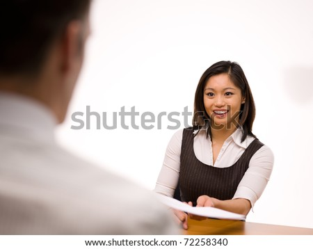 An asian woman giving her resume to a man at a job interview - stock photo