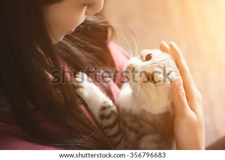 An Asian woman play with her kitten at home. - stock photo