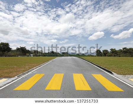 An asphalt road with a yellow zebra crossing on a soccer field leading to the goal mouth on a blue cloudy day. - stock photo