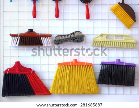 An assortment of brooms and brushes for household and cleaning purposes