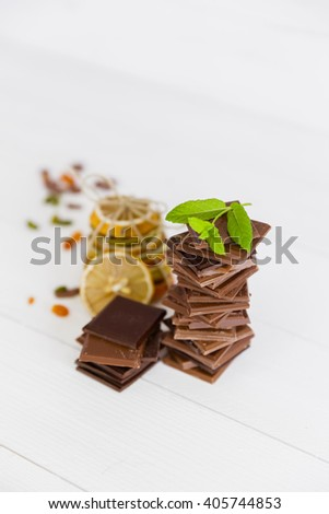 An assortment of dark and milk chocolate with chocolate milkshake and  dried fruits on wooden board - stock photo