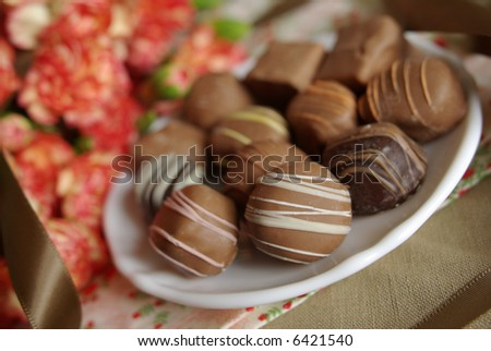 An assortment of fine chocolates with a bouquet of carnations in the background. Very shallow focus on white striped chocolate in foreground. - stock photo