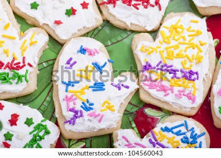 An assortment of homemade Christmas cookies decorated and in the shape of mittens. - stock photo