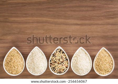 An assortment of rice in bowls, arranged as a border, over a wooden background - stock photo