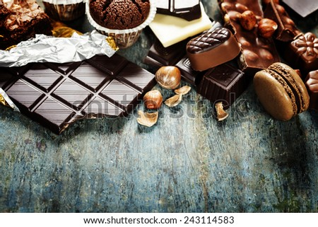 An assortment of  white, dark, and milk chocolate with nuts, muffins, macaroons - on wooden background - stock photo