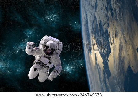 An astronaut floats above Earth. Stars provide the background.  Elements of this Image Furnished by NASA. - stock photo