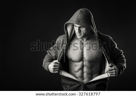 An athlete in a sports jacket with a hood on a dark background. A man shows his muscles revealing jacket. Photos for sporting magazines, posters and websites. - stock photo