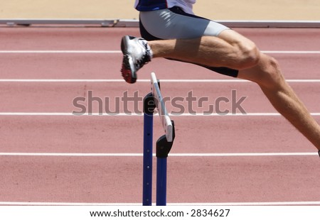 An athlete leaping the hurdles - stock photo
