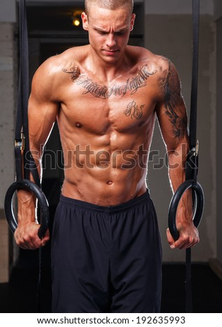 An athlete with tattooed body excercising in a gym - stock photo