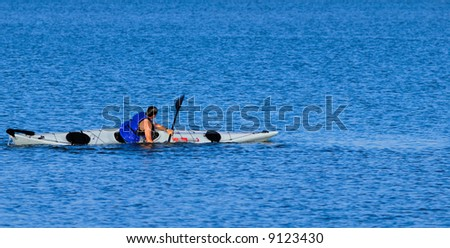 An athletic male kayaker performs float-asisted roll in calm waters of Mission Bay, San Diego, California. Copyspace on top and bottom. - stock photo