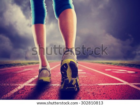 an athletic pair of legs going for a jog or run during sunrise or sunset - healthy lifestyle concept toned with a retro vintage instagram filter effect app or action  - stock photo