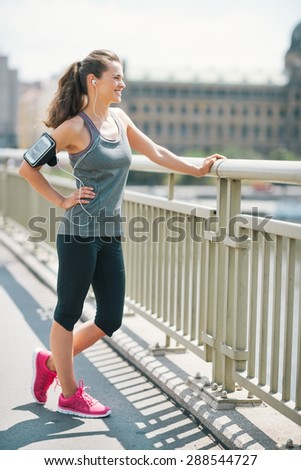 An athletic woman in pink sneakers stands on bridge, is relaxing, standing with a hand on her hip, while smiling and resting. Looking out at the city, she feels good. - stock photo
