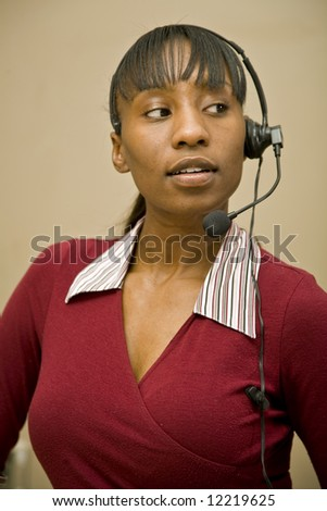 An attractive African American customer support representative, office worker or business woman. - stock photo