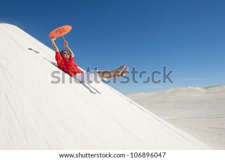 An attractive and confident looking mature woman with red blouse and umbrella, isolated on white sand dune overlooking a desert panorama, with clear blue summer sky as background and copy space. - stock photo