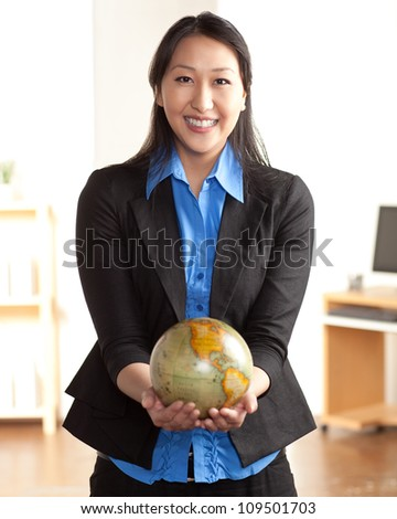 An attractive and happy young Asian woman holding a world globe wearing a black suite and blue shirt. - stock photo