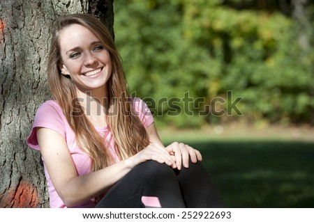 An attractive and happy young brunette girl sitting next to a tree on a sunny day. - stock photo