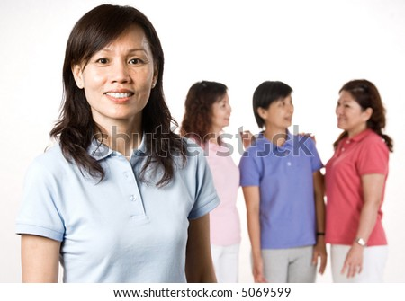 An attractive Asian woman in her 40s standing with a group of friends talking behind her - stock photo