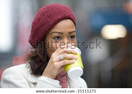 An attractive business woman enjoying a hot coffee in the city. - stock photo