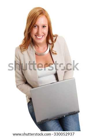 An attractive businesswoman in a tan jacket and jeans, red hair. Sitting down with a laptop computer in her lap. White background. - stock photo