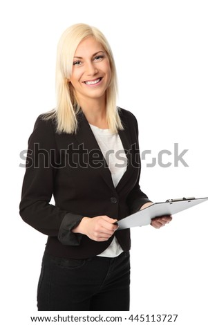 An attractive businesswoman wearing a black suit and white shirt, holding a clipboard, standing against a white background. - stock photo