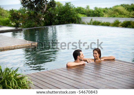 An attractive caucasian couple relaxing in an outdoor pool together - stock photo