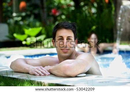 An attractive caucasian man relaxing in a jacuzzi pool outdoors - stock photo