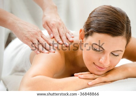 An attractive caucasian woman getting massaged in a spa - stock photo