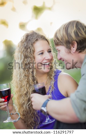 An Attractive Couple Enjoying A Glass Of Wine in the Park Together. - stock photo