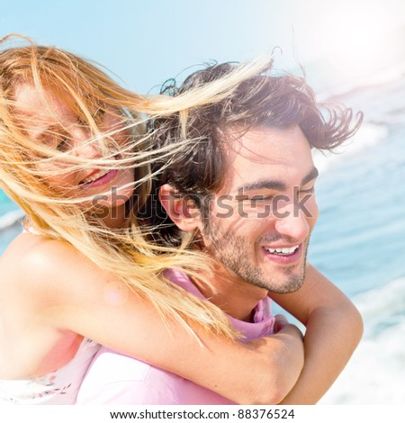 An attractive couple fooling around on the beach - stock photo