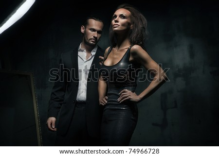 An attractive couple on the dark background - stock photo