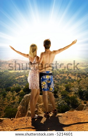 An attractive couple relaxing in high mountains and watching sunrise - stock photo