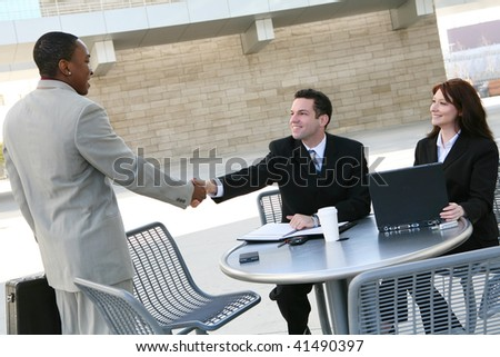 An attractive, diverse business man and woman team shaking hands at office building - stock photo