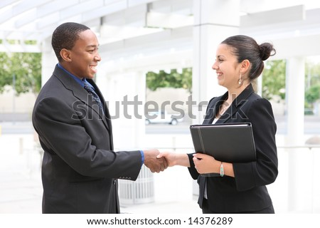 An attractive, diverse, business team man and woman handshake - stock photo
