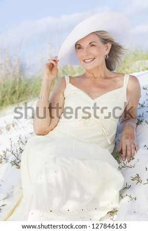 An attractive elegant classy senior woman in a yellow sun dress & white sun hat sitting on a white sand beach with grass and a blue sky behind her. - stock photo