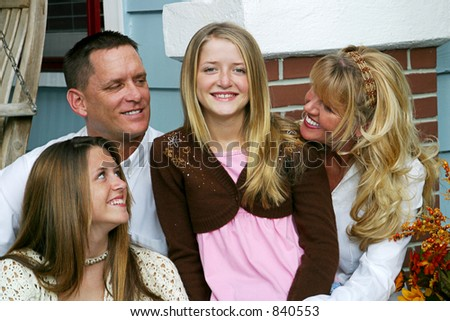 An attractive family all looking at the youngest girl in the center of the group. - stock photo