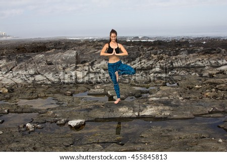 An attractive female doing yoga on the beach and smiling at the camera - stock photo