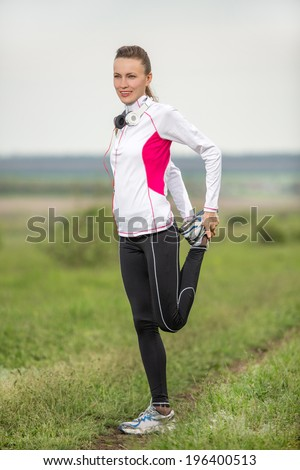 An attractive female runner stretching before her workout. Beautiful fit girl. Fitness model outdoors. Healthy lifestyle concept - stock photo