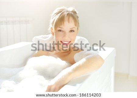 An Attractive girl relaxing in bath on light background - stock photo