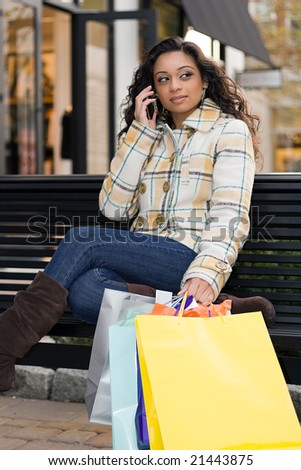 An attractive girl talking on her cell phone while out shopping in the city. - stock photo