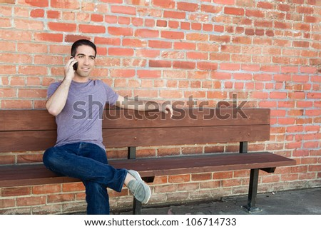 An attractive guy sitting on a wooden bench in front of a brick wall talking on a cellular phone looking off. - stock photo