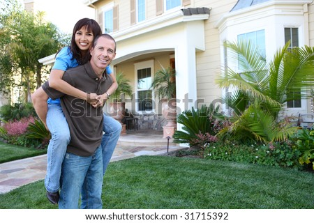 An attractive happy couple in front of their home in love - stock photo
