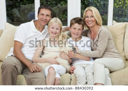 An attractive happy family of mother, father, son and daughter sitting on a sofa at home having fun with pet dog - stock photo