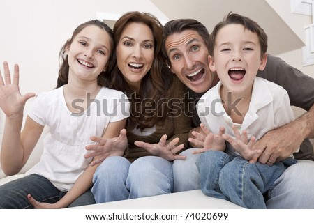 An attractive happy, laughing family of mother, father, son and daughter sitting on a sofa at home having fun - stock photo