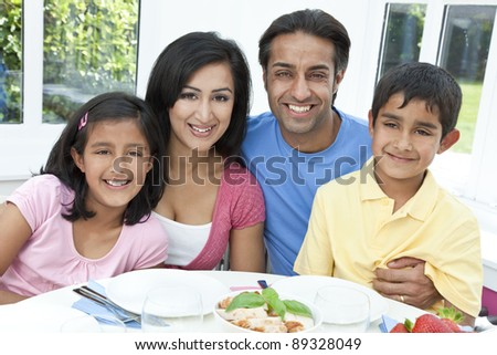 An attractive happy, smiling Asian Indian family of mother, father, son and daughter eating healthy food at a dining table. - stock photo