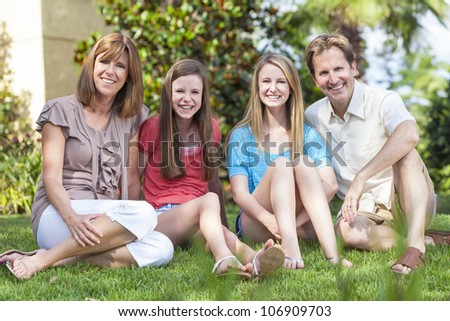 An attractive happy, smiling family of mother, father and two daughters sitting together outside in a garden. - stock photo