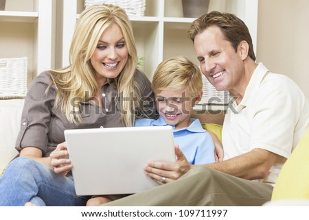 An attractive happy, young family of mother, father and son sitting on a sofa at home using a laptop computer - stock photo