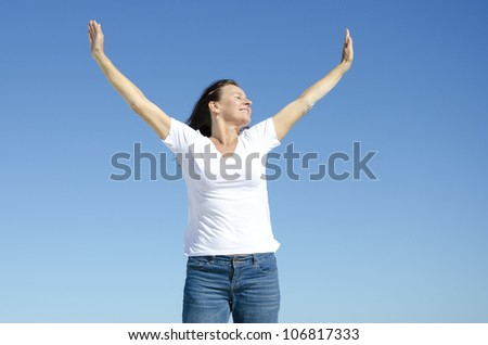 An attractive looking mature woman in her fifties showing her happy feelings by rising her arms up in the air, with a friendly smile and closed eyes, clear blue sky as background and copy space. - stock photo