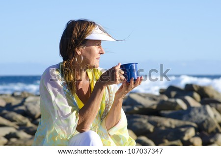 An attractive looking mature woman sitting relaxed at the ocean with cup of tea or coffee, isolated with sea and blue sky as background and copy space. - stock photo