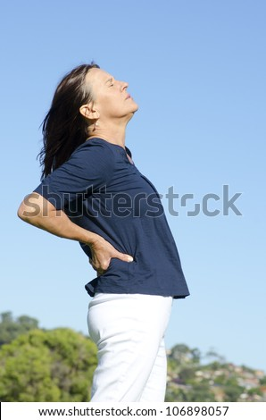 An attractive looking middle aged woman having back problems, feeling the pain in her body, with her eyes closed. Blue sky as background and copy space. - stock photo